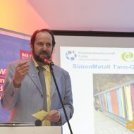 Bernhard Simon erklärt seine Gedanken zur farbenfrohen Toranlage